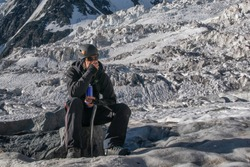 High altitude sickness. Climber breathing oxygen from the O2 tank on the background of glacier and covered with snow and ice mountains.