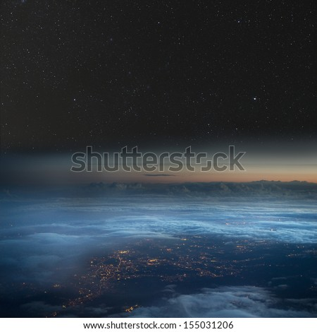 High altitude view of the Earth at night. City lights below the clouds, stars above.