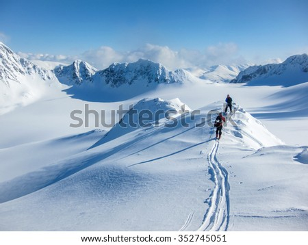 High altitude view of two skiers walking on a mountain ridge in the Lyngen Alps, Norway