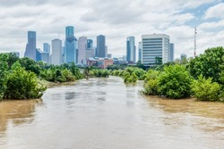 High and fast water rising in Bayou River with downtown Houston in background under cloud blue sky. Heavy rains from Harvey Tropical Hurricane storm caused many flooded areas in greater Houston area.