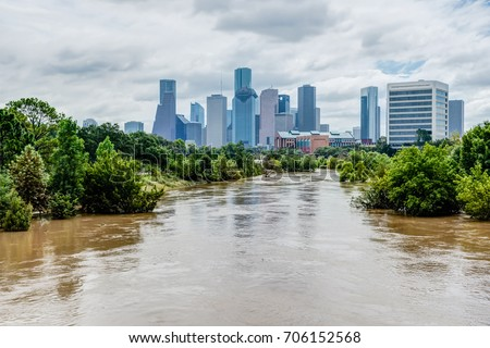 High and fast water rising in Bayou River with downtown Houston in background under cloud blue sky. Heavy rains from Harvey Tropical Hurricane storm caused many flooded areas in greater Houston area. #706152568