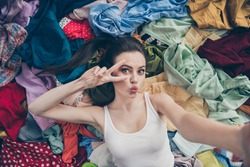 High angle above photo of lovely lady home spring cleaning lying many clothes stack floor prepared untidy stuff washing make selfies show v-sign symbol followers her stuff send kiss indoors