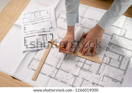 High angle above top view cropped concentrated focused clever intelligent lady in her formalwear shirt she stand at the table in light loft interior hold ruler in hand work with space on blank
