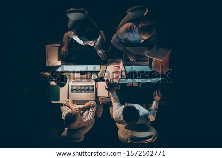 High angle above view photo of hard-working four busy business men women working overtime looking computer screen talking about startup lamp light dark office indoors