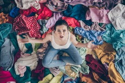High angle above view photo of stressed helpless lady stay home spring cleaning household sit many clothes stack floor pick select outfit nothing to wear concept all stuff dirty indoors