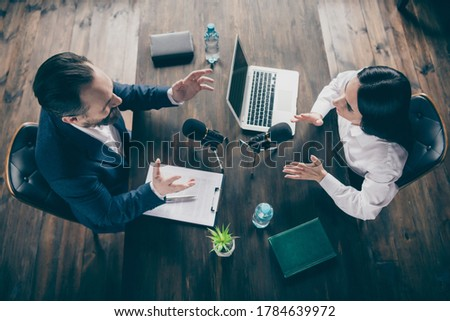 High angle above view photo of two business people journalism, press conference ask questions speak mic report politics information sit opposite modern office indoors