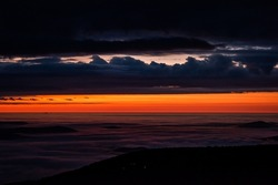 High angle abstract view above dark inversion clouds at sunrise morning in Wintergreen Resort, Virginia ski town with colorful red sunlight sky in Blue ridge