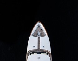 High angle aerial bird's eye partial view of the bow of a long white luxury yacht with wooden deck in dark blue waters shortly after sunset in Sydney, Australia with a lot of copy space.