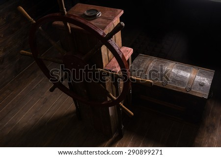 High Angle Chiarascuro of Antique Steering Helm with Wheel and Compass on Deck of Sailing Ship with Old Wooden Chest