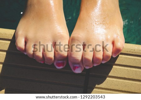 high angle close up view of little girl's wet feet resting on the edge of a swimming pool  #1292203543