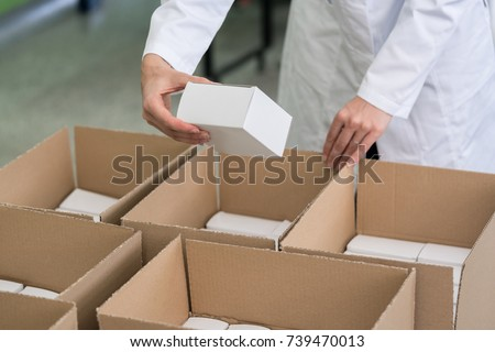 High-angle close-up view of the hands of a manufacturing worker putting packed products in cardboard boxes, before export or shipping during manual work in a cosmetics factory