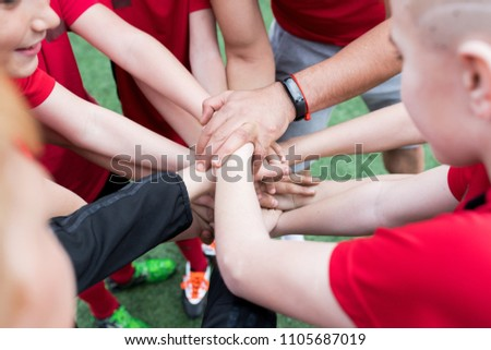 High angle closeup of junior football team stacking hands during motivational pep talk before match in outdoor stadium, copy space #1105687019