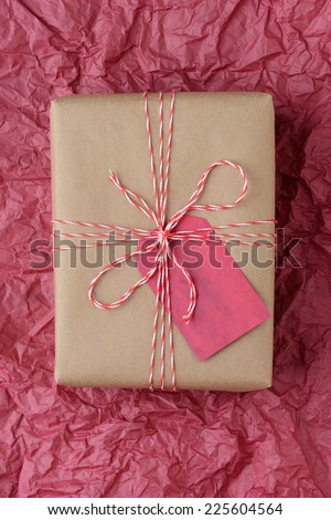 High angle closeup shot of a plain brown paper wrapped present tied with red and white string. The gift is on a piece of red tissue paper filling the frame, Vertical Format.
