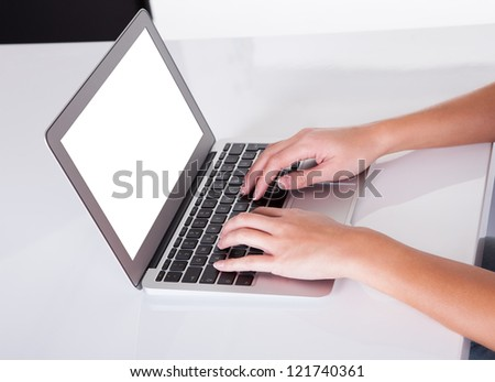 High angle cropped view image of female hands typing on a laptop keyboard with a blank white screen