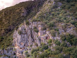 High angle drone aerial view of ancient greek rock cut tombs carved into cliffside in Myra (Demre, Turkey)