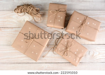 High angle image of four brown packages wrapped with plain brown paper on a white rustic wood table. Paper stars on the boxes that are tied with twine.
