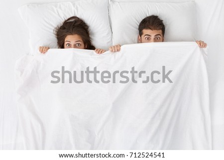 High angle indoor shot of funny adult couple lying in bed with blanket pulled up over their noses and staring at camera with surprised and shocked looks. Bedtime, love, romance and sex concept