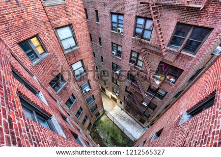 High angle, looking down view on illuminated brick apartment condo building .New York City with fire escapes, windows