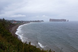 High angle northern view of the sea and beach in quaint Percé village, with the Cape Canon, the wharf and the iconic Rocher Percé seen during a rainy day, Quebec, Canada