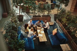 High angle of a diverse group of young businesspeople talking together during a casual meeting the the lounge area of an office