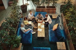 High angle of a group of diverse young businesspeople having a casual meeting together on sofas around a coffee table in an office lounge