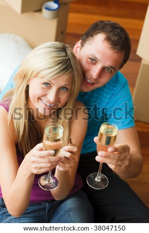 High angle of a happy couple celebrating new house with champagne smiling at the camera