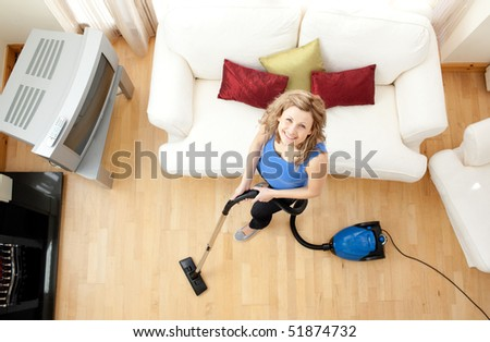 High angle of a mirthful woman vacuuming in the living-room
