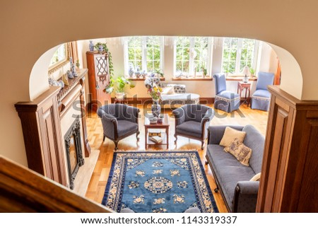 High angle of a rustical living room interior with a blue rug, armchairs, sofa and wooden floor
