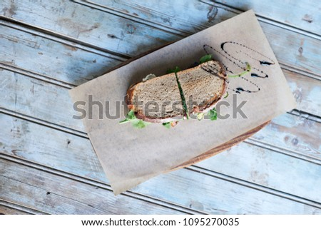 High angle of a vegetable sandwich resting on a piece of paper and board on a wooden table drizzled in balsalmic vinegar