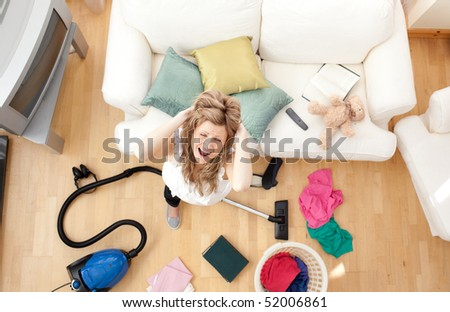 High angle of an irritate blond woman vacuuming the living-room