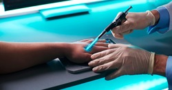 High angle of anonymous medical practitioner in gloves using modern tool to implant blue RFID microchip into hand of patient over table with futuristic scanner in laboratory