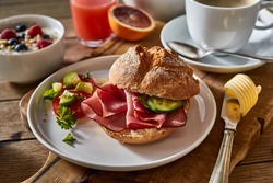 High angle of appetizing sandwich with ham and vegetables served on wooden cutting board for continental breakfast at home