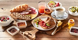 High angle of assorted appetizing food for continental breakfast placed on wooden table at home