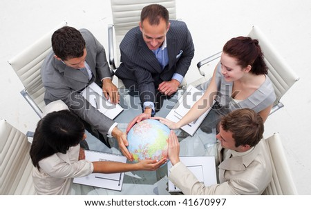 High angle of business people holding the world. Worldwide business