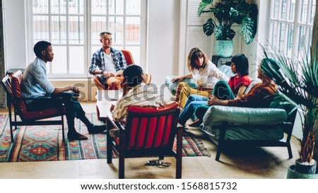 High angle of pensive adult multiracial business partners disputing while sitting at table in comfortable armchairs and on couch during discussion of future project at home.Meeting in coworking office