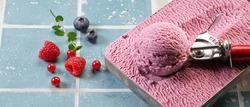 High angle of tasty gelato scoop in metal container with scooper near assorted bright juicy berries on tiled surface