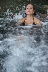 High angle of tranquil female lying in bubbling water of hot tub in spa center and enjoying vacation with closed eyes