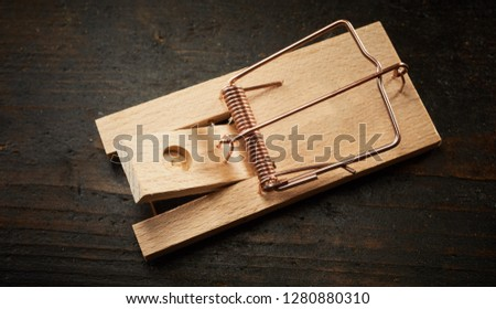 High angle of wooden mousetrap bar with cocked spring, sitting on dark floor without a bait