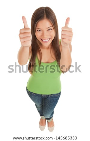 High angle perspective of a happy smiling young woman in jeans looking up at the camera giving giving a double thumbs up of success and approval isolated on white