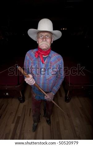 High angle portrait of a senior man in western wear, holding a pool cue and standing in a pool hall. He is looking at the camera with a serious expression. Vertical format.