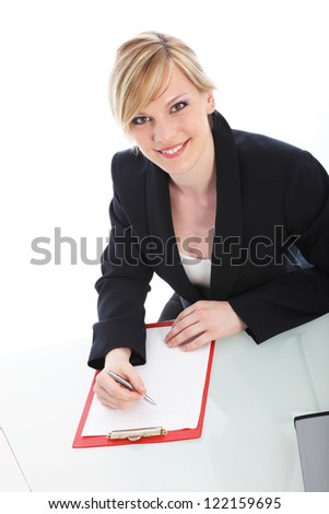 High angle portrait of an attractive young businesswoman writing on a blank sheet of paper on a clipboard and smiling up at the camera isolated on white