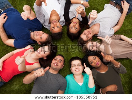High angle portrait of confident college students gesturing thumbs up while lying on grass #185558951
