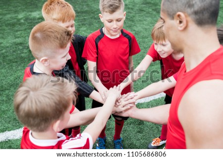 High angle portrait of junior football team stacking hands during motivational pep talk before match in outdoor stadium, copy space #1105686806