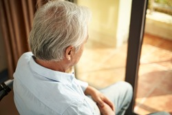 high angle rear view of a lonely asian old man sitting in wheel chair in nursing home
