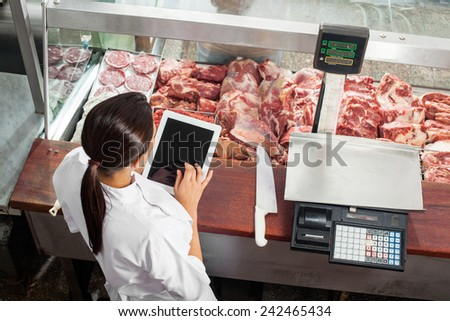 High angle rear view of female butcher using digital tablet at display counter in butchery