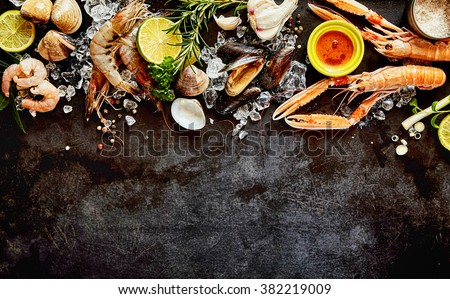 High Angle Seafood Cuisine Background Image with Fresh Shellfish - Shrimp, Langostino, Mussels and Clams - and Ingredients on Dark Background with Copy Space