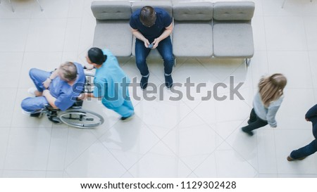 High Angle Shot in the Hospital Lobby, Young Man Waits for Results while Sitting and Using Mobile Phone, Doctors, Nurses and Patients Walk Past Him. Clean, New Hospital.