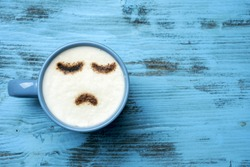 high-angle shot of a blue cup of cappuccino with a sad face drawn with cocoa powder on its milk foam, on a blue rustic table with a blank space on the right