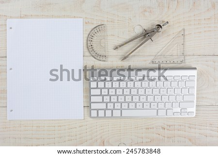 High angle shot of a computer keyboard next to a sheet of graph paper, a compass and protractor, on a whitewashed wood table, in a home office.