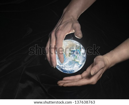 high angle shot of a shining crystal globe surrounded by black crinkly fabrics and two hands around